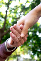 Elderly hand holding care taker hand